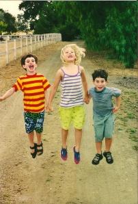 three kids jump for joy